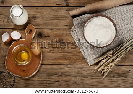 Flour in a bowl with ingredients for preparing baked products. Top view. Free space for text. Copy space - stock photo