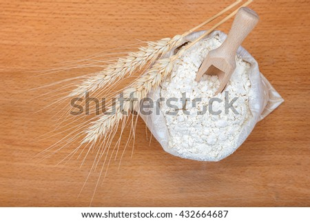 Flour in a canvas bag and wheat ears on a wooden background.