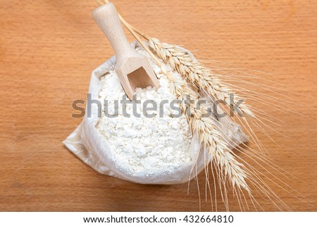 Flour in a canvas bag and wheat ears on a wooden background. - stock photo