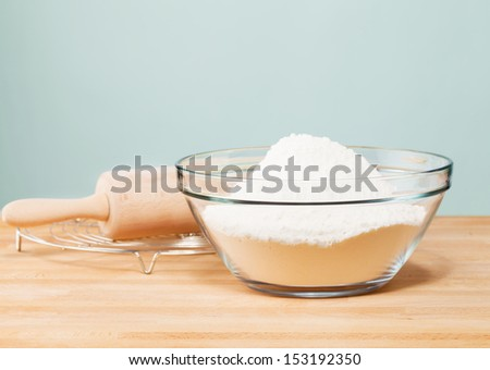 flour in a glass bowl with a rolling pin on with in front of a soft green wall - stock photo
