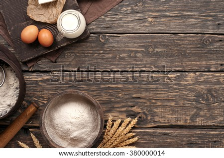 flour in a wooden bowl on dark wooden background with spikelets of wheat, eggs and milk, top view with copy space - stock photo