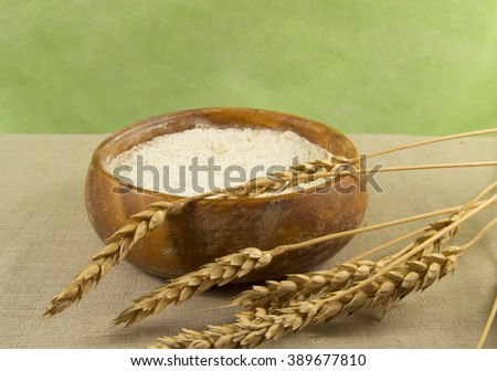 Flour in a wooden bowl with ears of wheat close up.