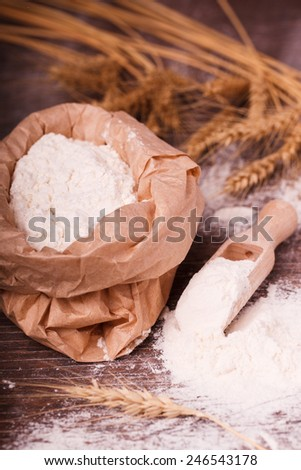 Flour in  bag and wooden spoon - stock photo