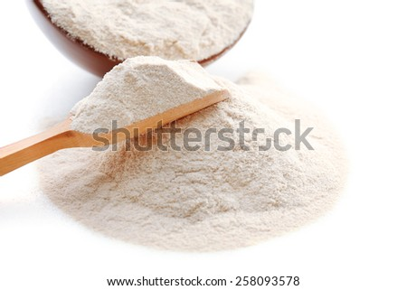 Flour in bowl and wooden spoon isolated on white - stock photo