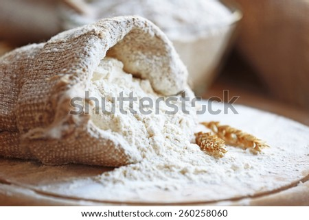 Flour in burlap bag on cutting board and wooden table background - stock photo