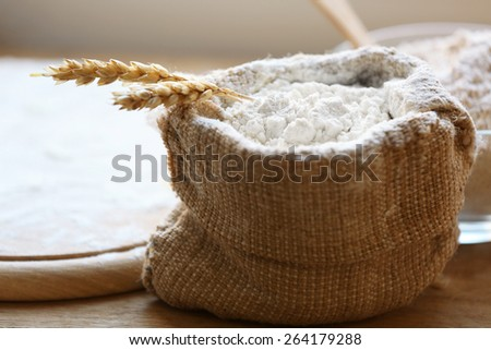 Flour in burlap bag with cutting board on wooden background - stock photo
