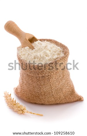 Flour in burlap sack and wooden spoon