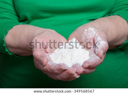 Flour in the woman's hand. Selective focus.