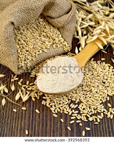 Flour oat in a wooden spoon, a bag of oaten grain, stalks on background of wood boards