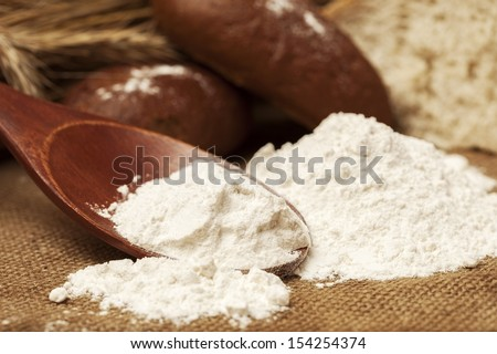 flour on a wooden spoon and bread - stock photo