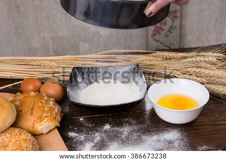 Flour sifter in action next to brown eggs, yolks and various rolls on wooden table with dried wheat stalks in background - stock photo