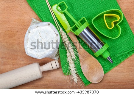 Flour with wheat ears, pastry syringe and baking molds on wooden background. Accessories for cooking.