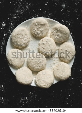 Floured homemade cookies prepared for baking, top view, vertical, toned