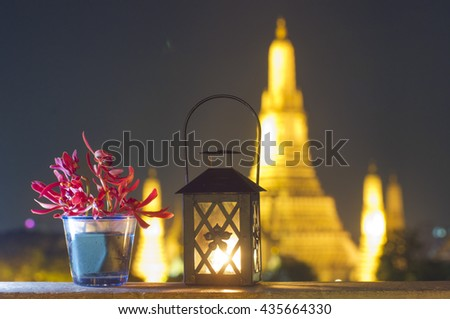 Flower and small lamp with the Wat Arun, The Temple of Dawn across river defocused. Postcard image. Bangkok, Thailand. - stock photo