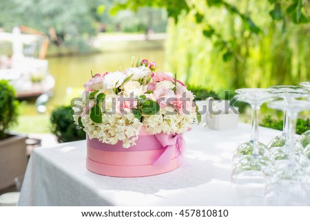 Flower arrangement in a hat box on the table, outdoor. Summer terrace of restaurant. - stock photo