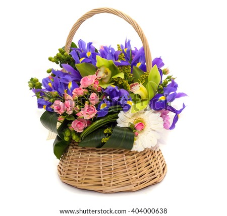 Flower arrangement in a wicker basket green for women with blue irises , white gerbera , green orchids and pink roses on a white background