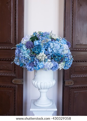 Flower arrangement of colorful summer blooms in a white pottery in front of the wooden door and white wall - stock photo