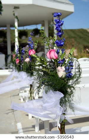 Flower arrangements on the pews at a wedding - stock photo