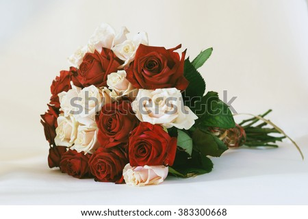 Flower bouquet from red and white roses isolated on white background. Closeup. Vintage toned photo - stock photo