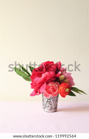 Flower bouquet in an old silver mug