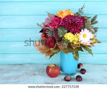 Flower bouquet in blue vase and apple on table on blue wooden wall background - stock photo