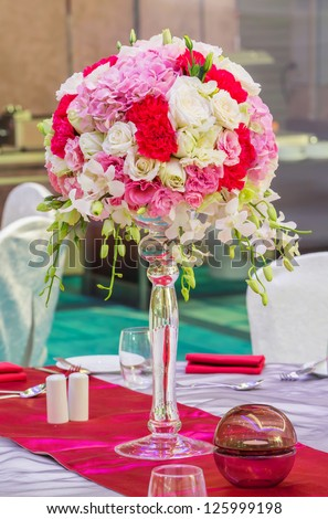 Flower bouquet in glass vase on dining table - stock photo
