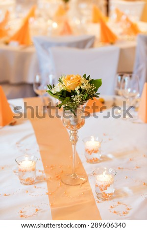 Flower bouquet in glass vase on wedding dining table - stock photo