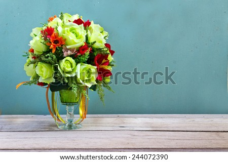 flower bouquet in glass vase on wood table grunge wall - stock photo