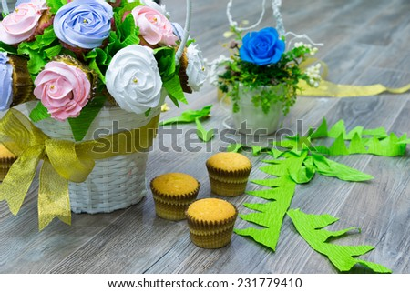 Flower bouquet of cupcakes, and other cupcakes on ground. Focus on cupcake rose flower on basket - stock photo
