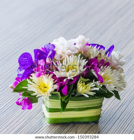 Flower bouquet of vanda, orchid, chrysanthemum on wood table - stock photo