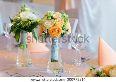 Flower bouquet on wedding dining table with glasses on background