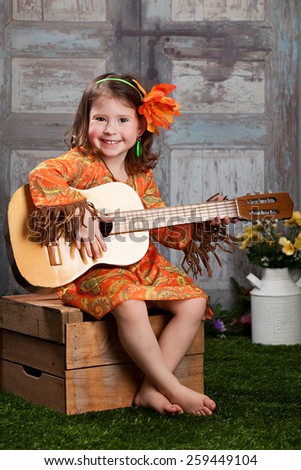 Flower Child.  Adorable preschooler dressed in retro 60's clothing, sitting on a crate, playing a guitar. - stock photo