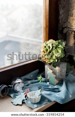 Flower Christmas: xmas decorations, candles and sweets set on old house window sill. Natural light, shallow focus on the tree decoration near flowers. Lightly toned photo. - stock photo
