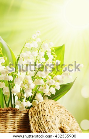 Flower composition with fragile lilies of the valley in the wicker basket - stock photo