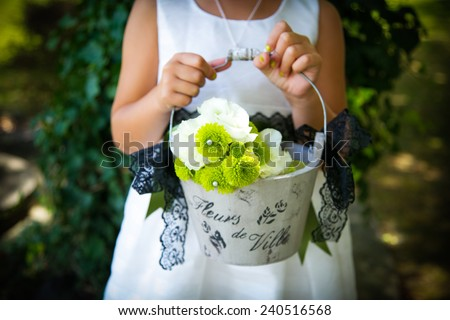 Flower girl at a wedding holding a basket of flowers. - stock photo