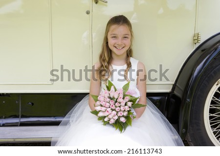 Flower girl (10-12) sitting on side of vintage car, smiling, portrait