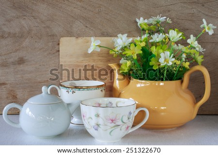 Flower in a yellow tea pot and vintage cup of coffee on wooden background, cozy home rustic decor, cottage living - stock photo