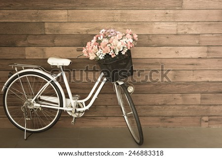 flower in basket of vintage bicycle on vintage wooden house wall - stock photo