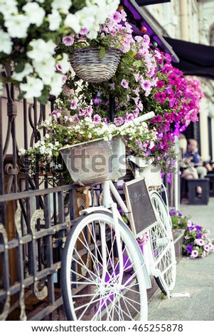 flower in basket of vintage bicycle on vintage wooden house wall, summer street cafe