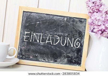 flower in white vase greeting card background with blackboard german for invitation - stock photo