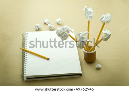 flower made of crumpled paper, notebook and pencil - stock photo