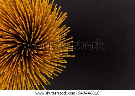 Flower of whole wheat spaghetti gathered in a bunch, view from top on stone plate