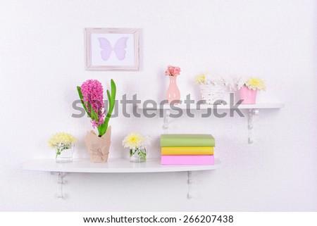 Flower on shelves on white wall background - stock photo