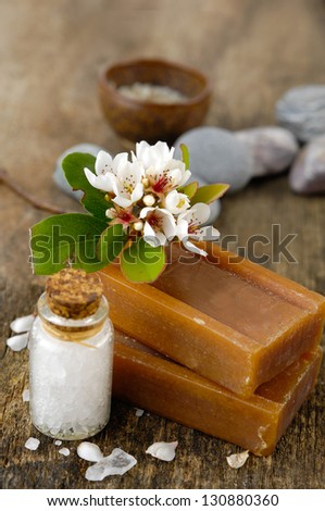 flower on soap, stones, salt in glass on old wooden