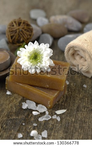 flower on soap, towel, soap ,stones, white flower petals on old wooden