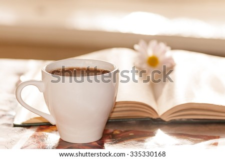 flower on the book, the Cup of black coffee in front of the window in the morning - stock photo