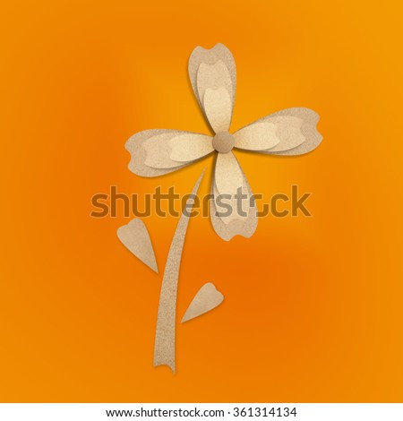 Flower origami recycled paper craft stick on an orange background. - stock photo