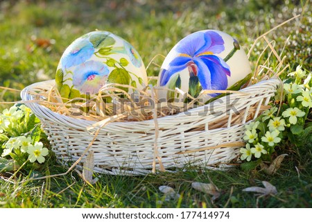 Flower painted eggs in a wicker basket . Easter and spring celebration - stock photo
