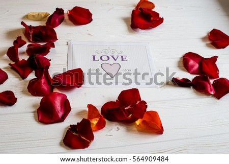 flower petals scattered around cards with the words love on a white wooden background