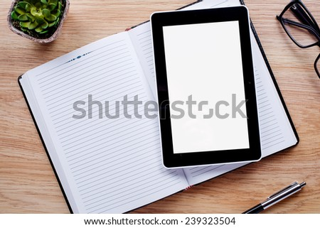 Flower pot, glasses, pen, notebook emphasizing copy space on the tablet screen on light brown desktop